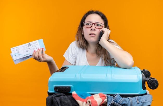 오렌지 벽을 통해 휴대 전화로 이야기하는 동안 놀라게하고 혼란스러워 보이는 항공 티켓을 들고 옷으로 가득 찬 가방으로 서있는 흰색 티셔츠에 젊은 여행자 여자