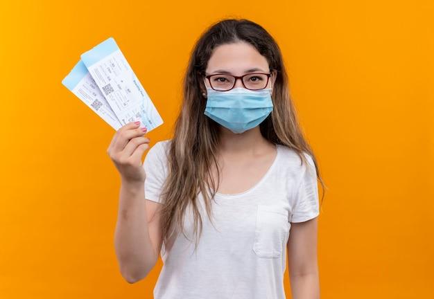오렌지 벽 위에 자신감 서 미소 항공 티켓을 들고 보호 페이셜 마스크를 착용하는 흰색 티셔츠에 젊은 여행자 여자