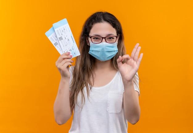 오렌지 벽 위에 서 확인 서명 하 고 웃 고 항공 티켓을 들고 보호 얼굴 마스크를 착용하는 흰색 티셔츠에 젊은 여행자 여자