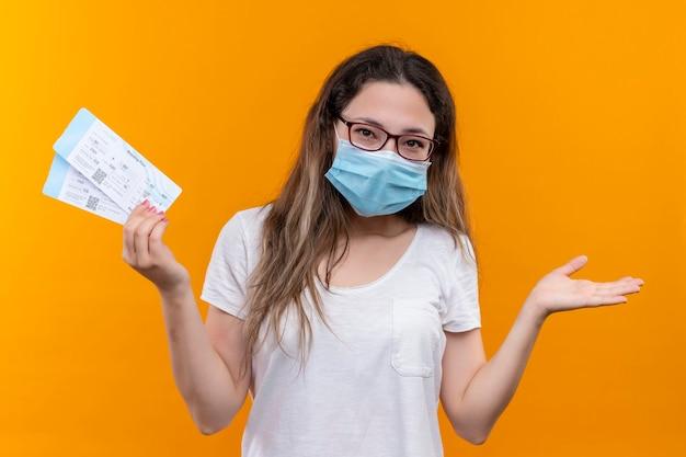 오렌지 벽 위에 서있는 손을 제기 미소 항공 티켓을 들고 보호 얼굴 마스크를 착용하는 흰색 티셔츠에 젊은 여행자 여자