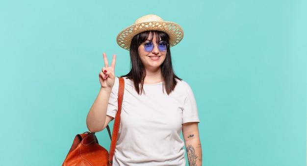 若い旅行者の女性は笑顔でフレンドリーに見え、前に手を前に2番目または2番目を示し、カウントダウン