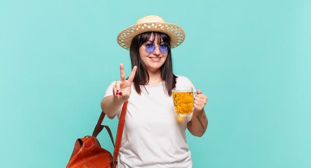 若い旅行者の女性は笑顔で幸せそうに見え、のんきで前向きで、片手で勝利または平和を身振りで示す