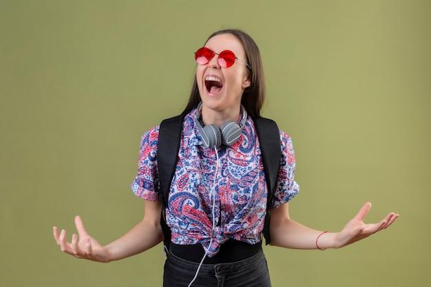 Молодая женщина-путешественница, стоящая с рюкзаком и наушниками в красных солнцезащитных очках, сумасшедшая и безумная, кричит с агрессивным выражением лица и поднятыми руками на зеленом фоне