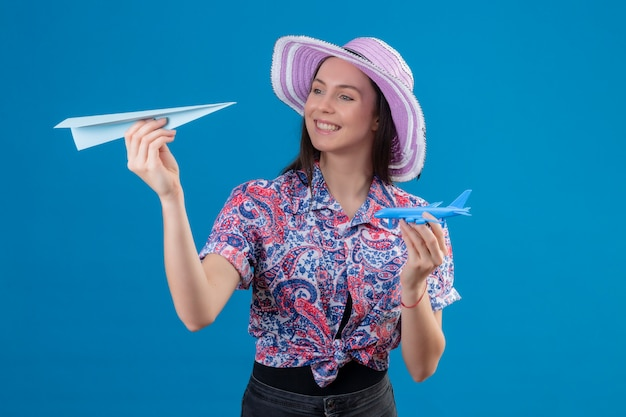 Donna giovane viaggiatore in cappello estivo tenendo carta e aeroplanini giocattolo, giocando con loro positivo e felice sulla parete blu