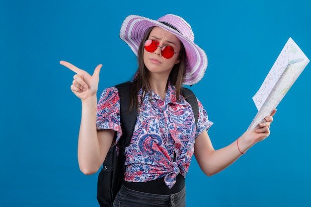 Giovane donna del viaggiatore in cappello estivo che indossa occhiali da sole rossi che tengono mappa che osserva da parte con espressione pensierosa che punta con il dito al lato pensando di avere dubbi in piedi su sfondo blu