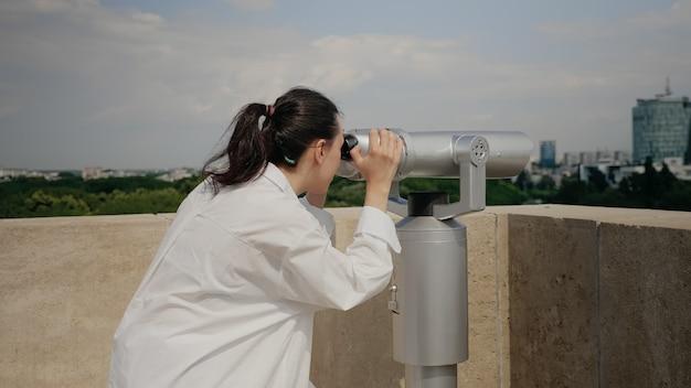 건물 지붕에 쌍안경을 사용하는 젊은 여행자 여성