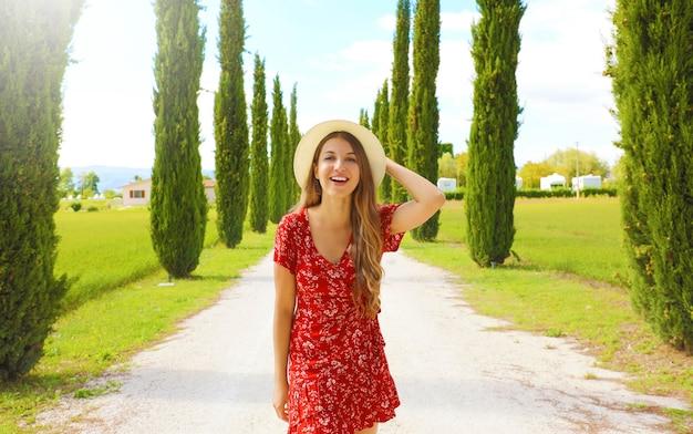 イタリアのヒノキのレーンを歩く若い旅行者の女性。