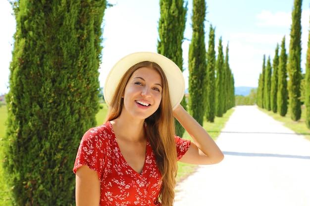 晴れた日にヒノキのレーンを歩く若い旅行者女性
