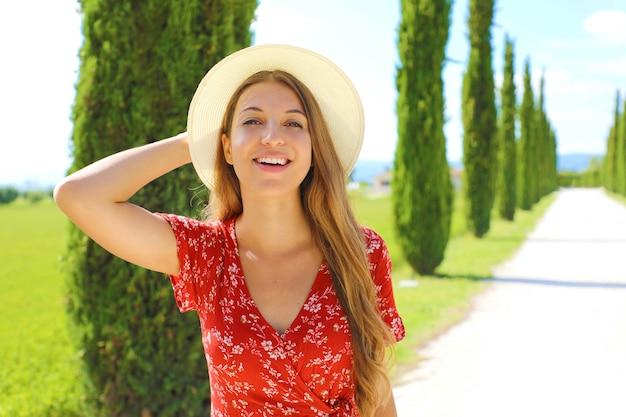 糸杉の車線を歩く若い旅行者女性