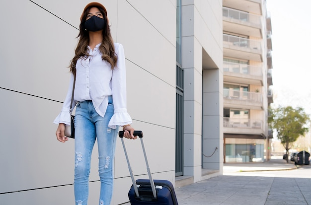 Молодой путешественник женщина в защитной маске и чемодан переноски во время прогулки на открытом воздухе по улице.