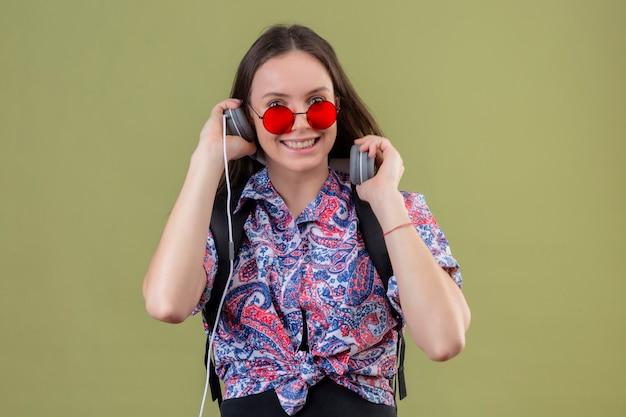 Молодая женщина-путешественница в красных солнцезащитных очках с рюкзаком слушает музыку в наушниках, улыбаясь со счастливым лицом, стоящим на зеленом фоне