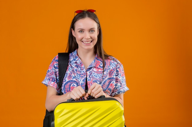 Young traveler woman wearing red sunglasses on head standing with backpack holding suitcase looking at camera smiling cheerfully with happy face over isolated orange background