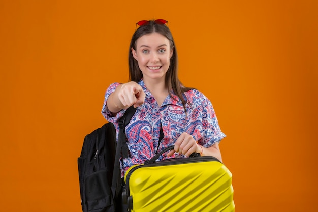 Young traveler woman wearing red sunglasses on head standing with backpack holding suitcase looking at camera smiling cheerfully with happy face pointing with index finger to camera over isolat