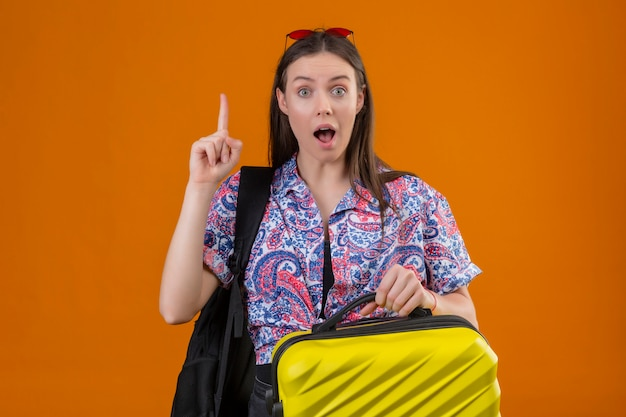 Young traveler woman wearing red sunglasses on head with backpack holding suitcase looking surprised and amazed standing with finger up, new idea concept over orange wall