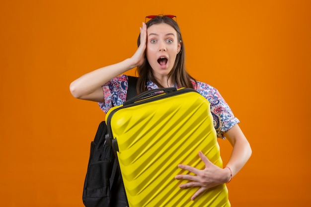 Young traveler woman wearing red sunglasses on head with backpack holding suitcase looking surprised and amazed with hand on head and wide open mouth and eyes over orange wall
