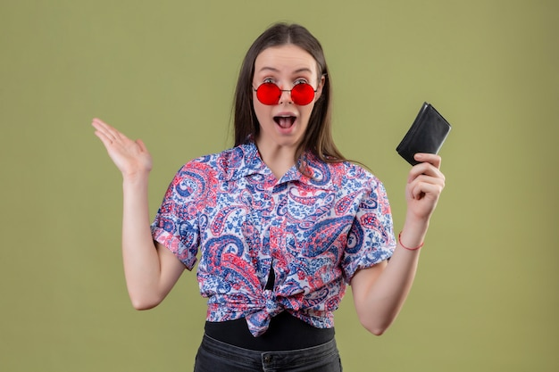 Young traveler woman wearing red sunglasses holding wallet looking amazed and surprised with arms raised over green wall