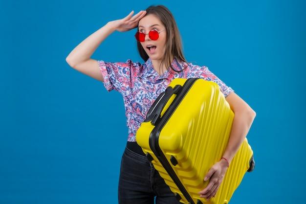Молодая женщина-путешественница в красных солнцезащитных очках держит желтый чемодан, смотрит вдаль с рукой, чтобы выглядеть позитивно и удивлена, стоя на синем фоне