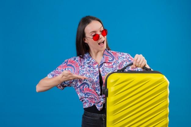 Молодая женщина-путешественница в красных солнцезащитных очках держит желтый чемодан, указывая рукой на int, радостно глядя на синем фоне