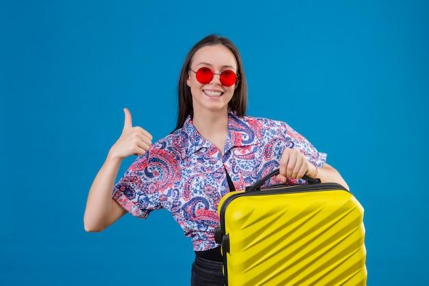 Молодая женщина путешественника нося красные солнечные очки держа желтый чемодан усмехаясь жизнерадостно показывая большие пальцы руки вверх над голубой стеной