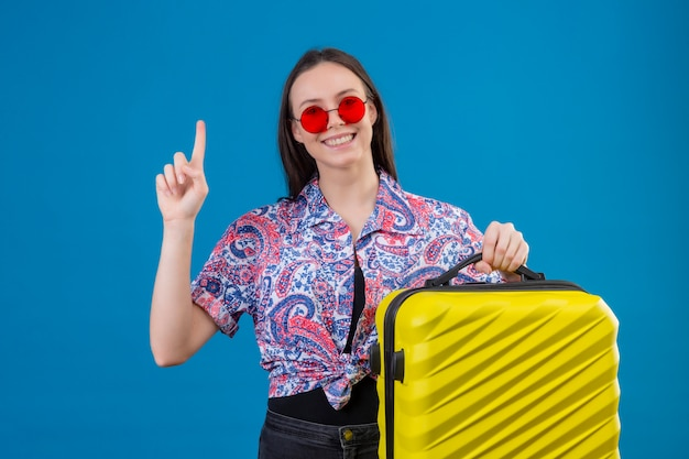 Young traveler woman wearing red sunglasses holding yellow suitcase with finger up looking confident having great idea over blue wall
