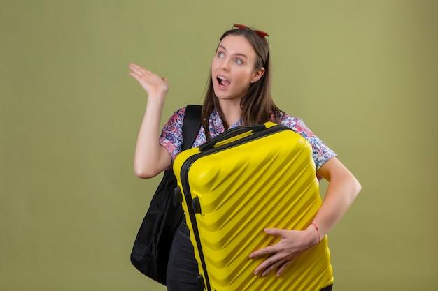 Молодая женщина-путешественница в красных солнцезащитных очках на голове, стоя с рюкзаком, держащим чемодан, глядя в сторону и представляя рукой что-то улыбаясь со счастливым лицом на зеленом фоне