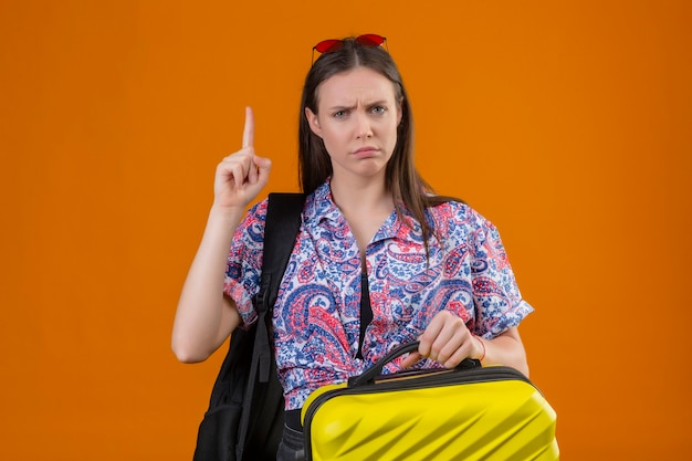 Молодая женщина-путешественница в красных очках на голове, стоя с рюкзаком, держащим чемодан, смотрит в камеру, хмурится, стоя с пальцем вверх, предупреждая об опасности на оранжевом фоне