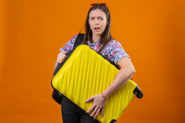 Молодая путешественница в красных солнцезащитных очках на голове стоит с рюкзаком, держащим чемодан, выглядит смущенным на оранжевом фоне