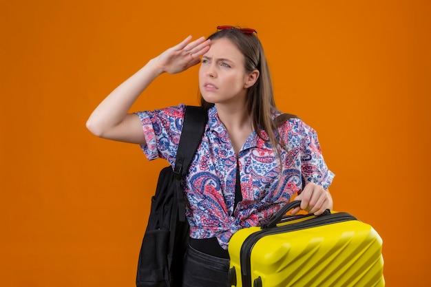 Молодая женщина-путешественница в красных солнцезащитных очках на голове стоит с рюкзаком, держащим чемодан, глядя вдаль рукой, чтобы посмотреть что-то на оранжевом фоне