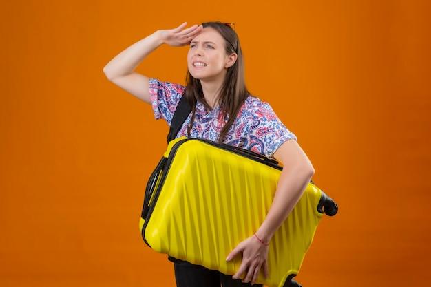 オレンジ色の背景に何かを見るために手で遠くを見てスーツケースを持ってバックパックで頭立っている赤いサングラスをかけている若い旅行者女性