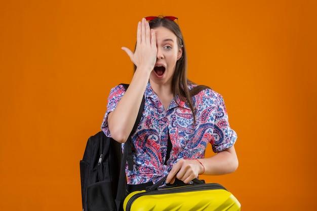 オレンジ色の背景の上に立っている目を覆っている顔に手で驚いて、驚いて探しているスーツケースを持ってバックパックで頭立っている赤いサングラスをかけている若い旅行者女性