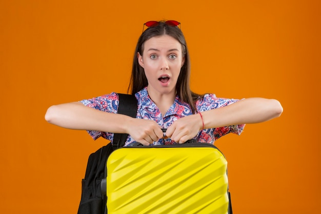 Молодая женщина-путешественница в красных солнцезащитных очках на голове, стоя с рюкзаком, держащим чемодан, выглядит удивленной и пораженной с широко открытым ртом и глазами на оранжевом фоне