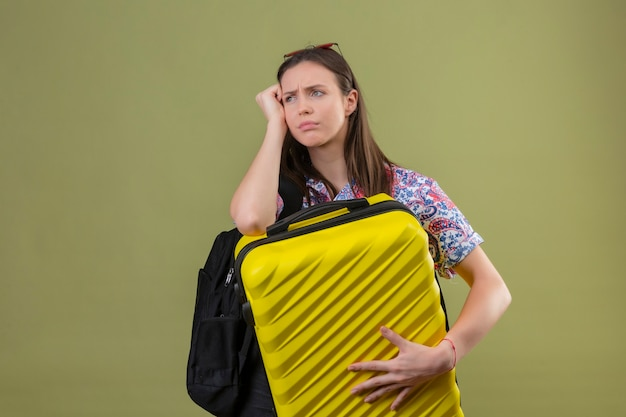 緑の背景で不幸な顔の近くの手で待っている疲れて待っているスーツケースを持ってバックパックで頭立っている赤いサングラスをかけている若い旅行者女性
