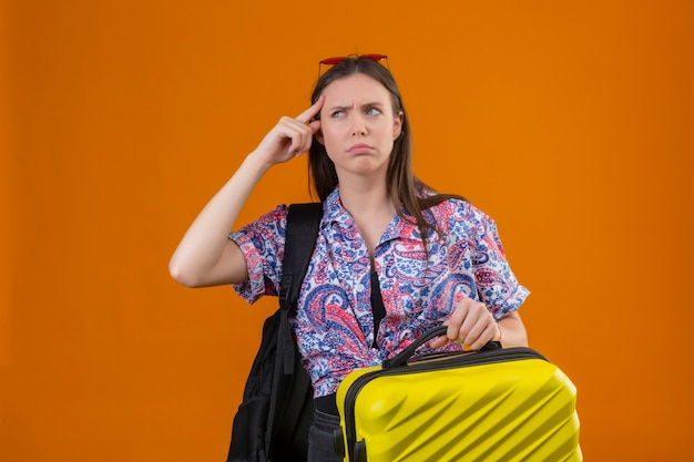 Молодая женщина-путешественница в красных солнцезащитных очках на голове, стоящая с рюкзаком, держащая чемодан, указывающая на храм с нахмуренным лицом, вспоминает, что не должна забывать о важных вещах, стоя над ораном