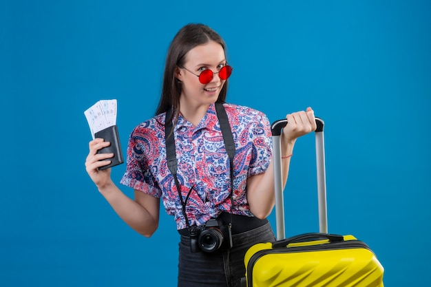 Young traveler woman wearing red sunglasses standing with yellow suitcase holding passport and tickets smiling cheerfully looking at camera with happy face over blue background