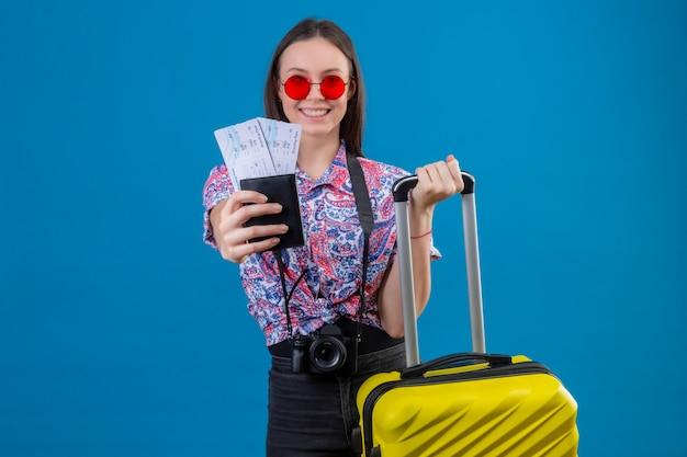 Giovane viaggiatore donna che indossa occhiali da sole rossi in piedi con la valigia gialla che mostra il passaporto e biglietti sorridendo allegramente guardando la fotocamera con la faccia felice su sfondo blu