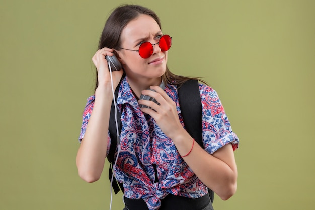 Young traveler woman wearing red sunglasses and with backpack listening to music using headphones displeased with frowning face over green wall
