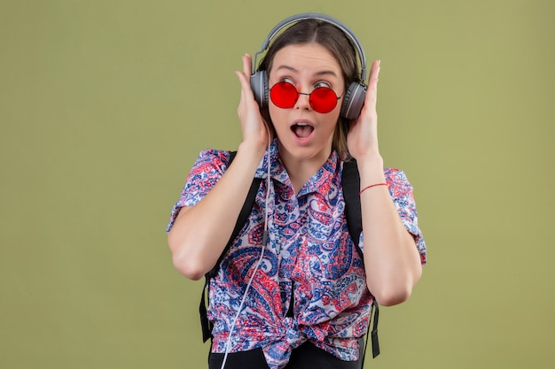 Young traveler woman wearing red sunglasses and with backpack listening to music using headphones looking surprised over green wall