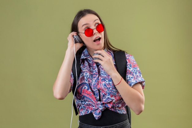 Young traveler woman wearing red sunglasses and with backpack listening to music using headphones looking surprised and happy over green wall