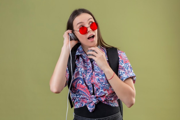 Donna giovane viaggiatore che indossa occhiali da sole rossi e con zaino ascoltando musica utilizzando le cuffie guardando sorpreso e felice in piedi su sfondo verde