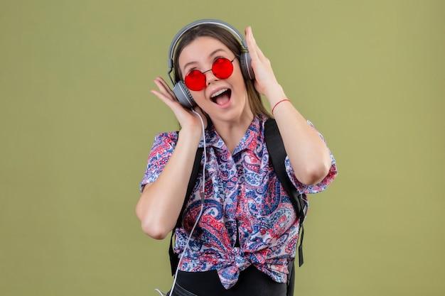 Giovane donna del viaggiatore che indossa occhiali da sole rossi e con lo zaino che ascolta la musica usando le cuffie che canta con la faccia felice che sta sopra fondo verde