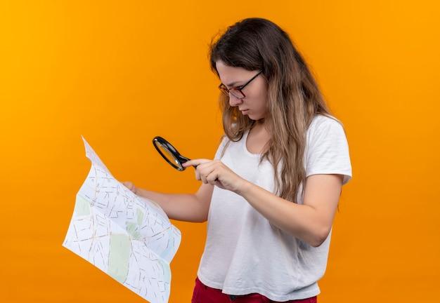 Giovane donna del viaggiatore in t-shirt bianca che tiene mappa guardandolo attraverso la lente di ingrandimento con espressione pensierosa sulla faccia pensando in piedi sopra la parete arancione