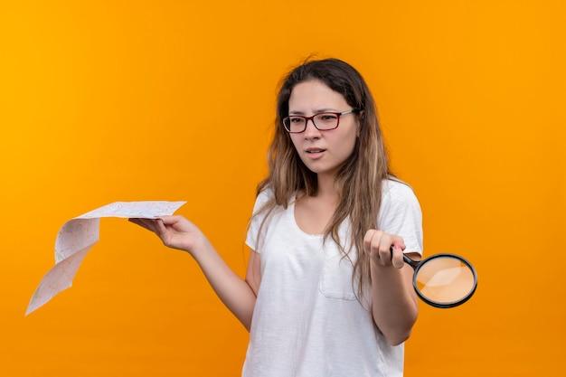 Giovane donna del viaggiatore in maglietta bianca che tiene mappa e lente d'ingrandimento alla ricerca, spalle alzate confuse in piedi sopra la parete arancione