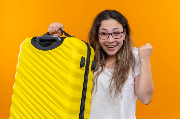 Young traveler woman in white t-shirt  holding suitcase excited and happy clenching fist standing over orange wall