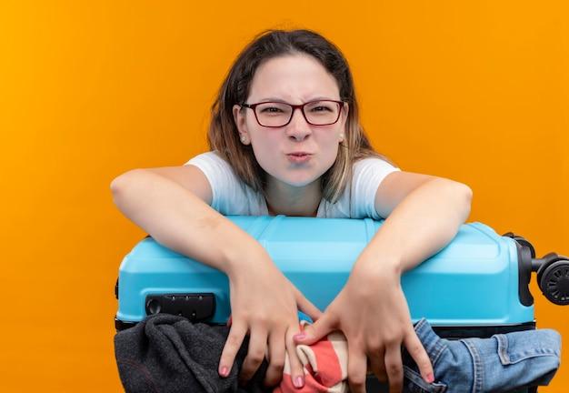 Giovane donna del viaggiatore in t-shirt bianca che tiene la valigia piena di vestiti accigliato cercando in piedi