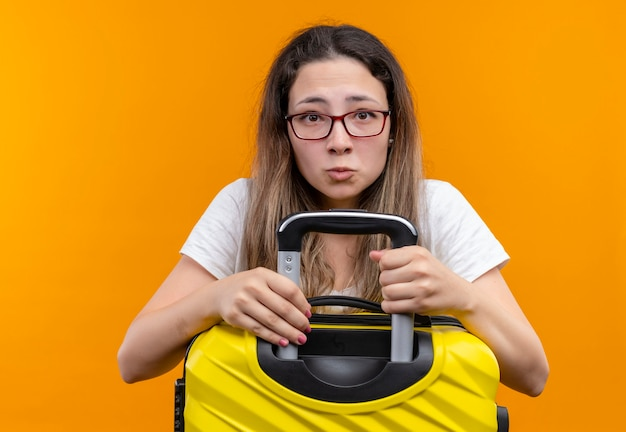 Donna giovane viaggiatore in t-shirt bianca che tiene la valigia guardando con espressione triste sul viso in piedi sopra la parete arancione