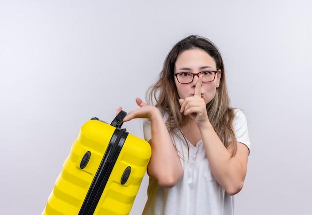 Giovane donna del viaggiatore in maglietta bianca che tiene la valigia che fa gesto di silenzio con il dito sulle labbra in piedi sopra il muro bianco