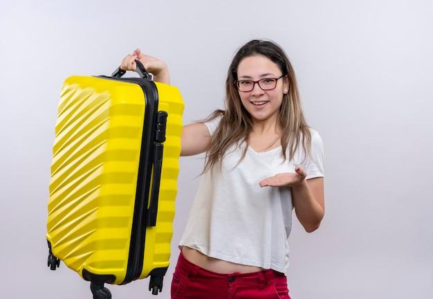 Donna giovane viaggiatore in t-shirt bianca che tiene la valigia presentandolo con il braccio della sua mano in piedi sul muro bianco