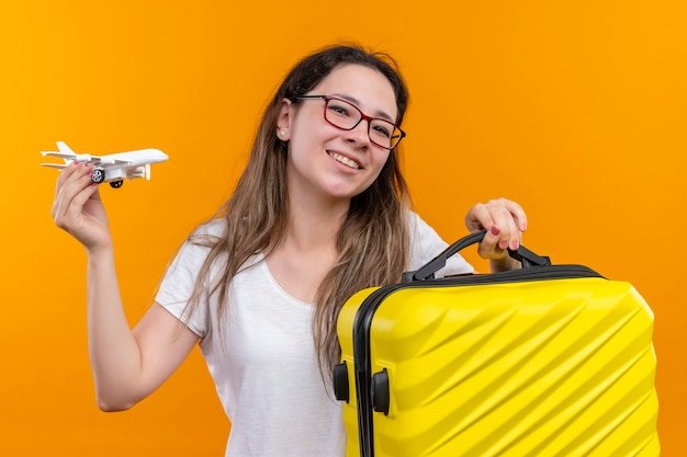 Young traveler woman in white t-shirt  holding travel suitcase  and toy airplane smiling cheerfully standing over orange wall
