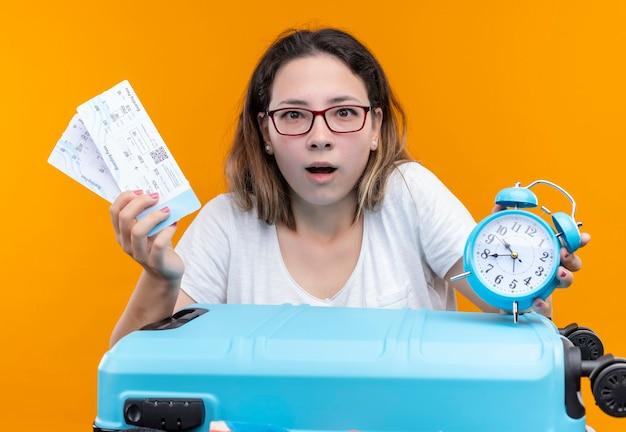 Giovane donna del viaggiatore in maglietta bianca che sta con la valigia piena di vestiti che tengono i biglietti aerei e la sveglia che sembra sorpresa e stupita sopra la parete arancione