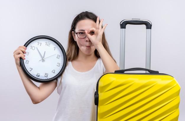 Giovane donna del viaggiatore in maglietta bianca che sta con l'orologio di parete della tenuta della valigia che fa segno giusto guardando attraverso questo segno sopra il muro bianco